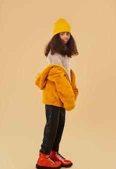 Модная хипстерская девочка-подросток с длинными вьющимися волосами, одетая в яркую зимнюю одежду и сапоги, стоящие на бежевом фоне, вид сбоку в полный рост