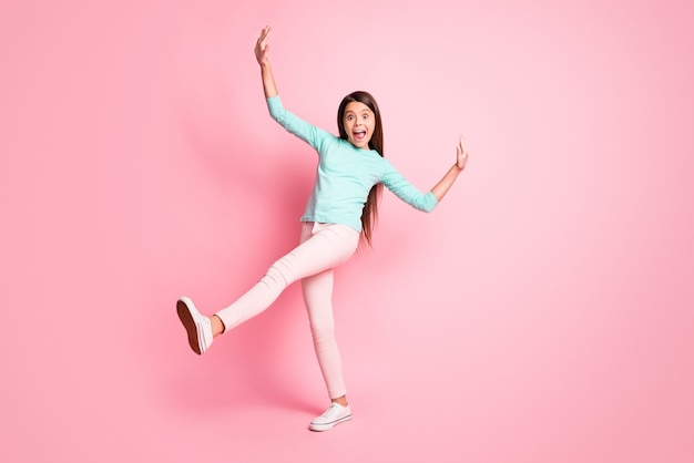 Фото в полный рост симпатичной милой маленькой латинской леди, длинные прически, танец, ретро-дискотека, поднять руки вверх, ноги, носить бирюзовую толстовку, брюки, белые кроссовки, изолированный розовый цвет фона