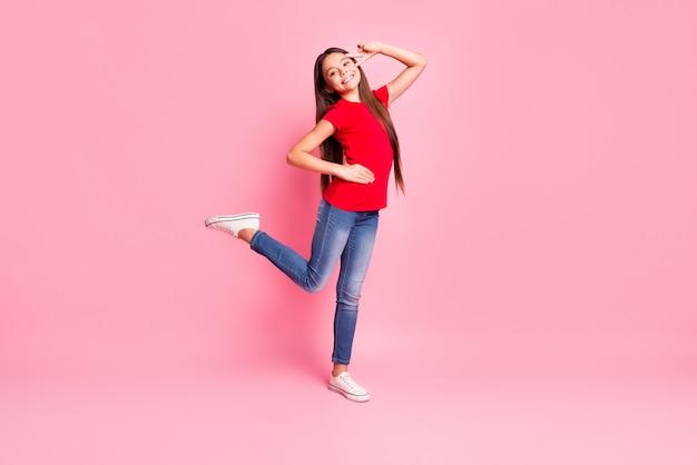 Фото в полный рост прекрасной милой маленькой леди, длинное шоу причесок, v-знак, танец, поднять ногу, бедро, зубастая улыбка, носить повседневную красную футболку, джинсы, кроссовки, изолированный розовый цвет фона