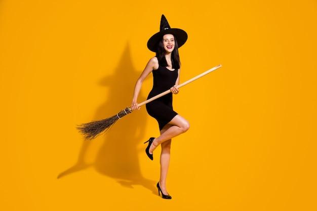かなり魅力的な若い魔術師の女性の笑顔の全身サイズの写真は、ほうきの柄のふりをします。