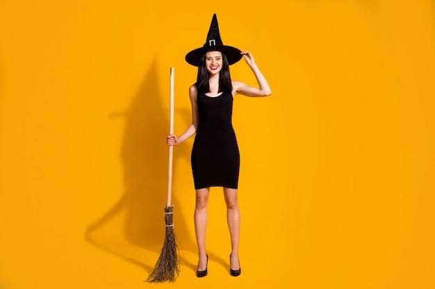 かなり素敵な若い魔術師の女性の全身サイズの写真は、ウィッチャーを引き付けるホールドほうきの帽子を笑顔で黒の帽子をかぶるハイヒールのドレスは明るい黄色の背景を分離しました