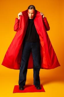 Стройная женщина в полный рост с креативным макияжем поправляет стильное мешковатое пальто, стоя на листе красной бумаги на желтом фоне