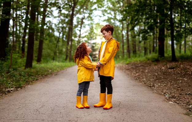 Full body of smiling little girl and older brother with red hair dressed in bright yellow raincoats and gumboots holding hands and looking at each other, while standing in walkway in green forest