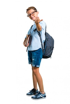 Full body of student boy with backpack and glasses presenting and inviting to come