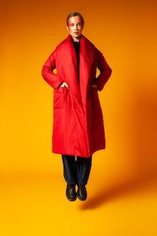헐렁한 빨간 코트 주머니에 손을 넣고 노란색 배경에 뛰어드는 동안 카메라를 바라보는 전신 세련된 젊은 여성