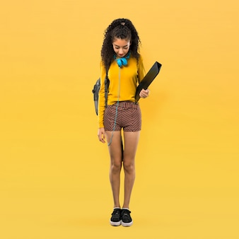Full body of teenager student girl with curly hair standing and looking down on yellow background
