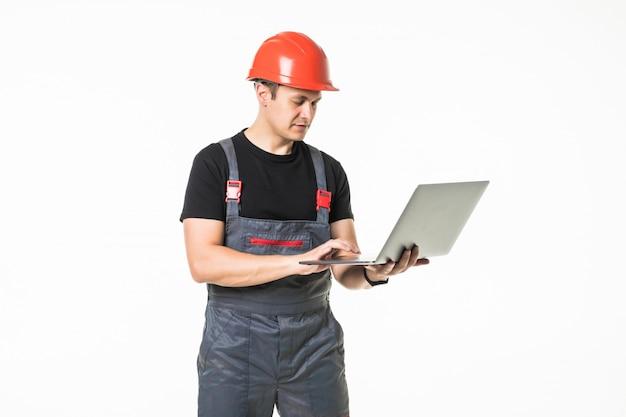 白い背景の上の彼のラップトップに取り組んでいる建設請負業者の全身ビュー