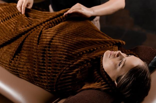 초콜릿 마사지 후 전신 랩. 스파에서 여성 모델을위한 미용 치료.