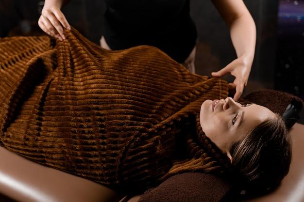 스파에서 여성 모델을위한 초콜릿 마사지 뷰티 트리트먼트 후 따뜻한 담요로 전신 랩.