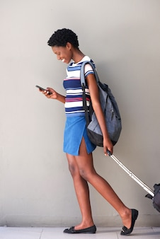 Full body young african woman walking with travel bag and using mobile phone