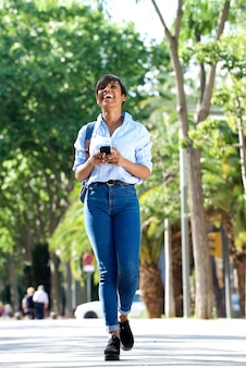 Full body young black lady walking with mobile phone outside