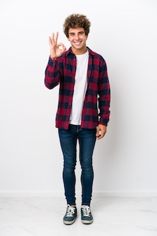 Full body young caucasian man isolated cheerful and confident showing ok gesture.