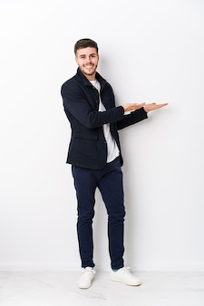 Full body young caucasian man isolated holding a copy space on a palm.