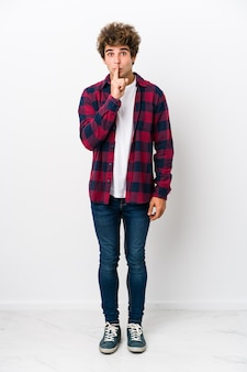 Full body young caucasian man isolated keeping a secret or asking for silence.