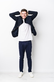 Full body young caucasian man isolated laughs joyfully keeping hands on head. happiness concept.