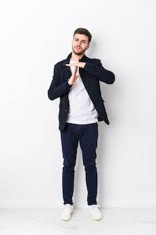 Full body young caucasian man isolated showing a timeout gesture.