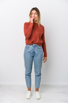 Full body young caucasian woman biting fingernails, nervous and very anxious.