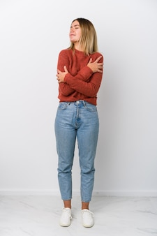 Full body young caucasian woman hugs, smiling carefree and happy.