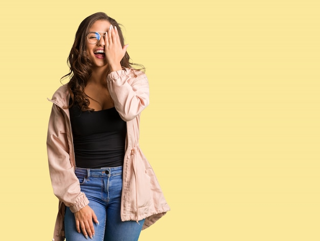 Full body young curvy woman shouting happy and covering face with hand