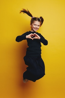 Молодая милая девушка всего тела улыбается и показывает жест сердца во время прыжка