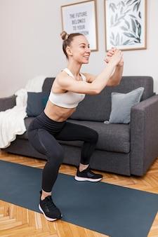 自宅でのフィットネストレーニング中に笑顔としゃがむスポーツウェアの全身若い女性アスリート