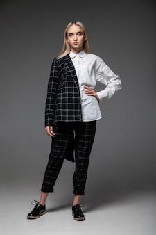 頭に触れ、灰色の背景に寄りかかってトレンディなスマートカジュアルな服を着た全身の若い女性モデル