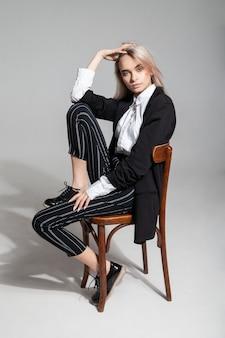 トレンディなスマートカジュアルな服を着た全身の若い女性モデルは、灰色の背景に椅子に座って頭に触れ、後ろにもたれかかっています