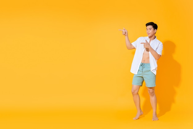 Full body of young handsome asian man in casual summer outfit pointing hands to copy space aside on colorful yellow wall