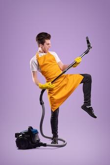 紫色の背景に対して家庭のルーチン中にギターのような掃除機を演奏するふりをしている黄色のエプロンと手袋の全身の若い男