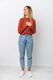 Full body young woman laughing keeping hands on heart