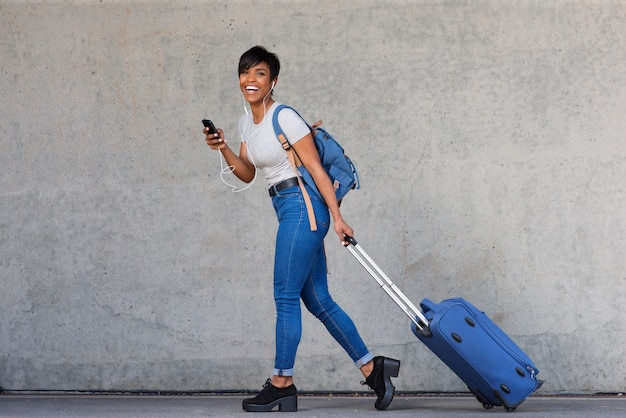 Full body young woman walking with travel bag and mobile phone