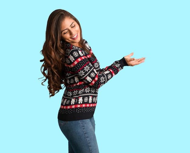 Полное тело молодая женщина, носить рождественский свитер, держа что-то с руками