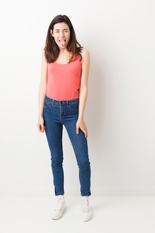 Full body young woman on white background funny and friendly sticking out tongue.