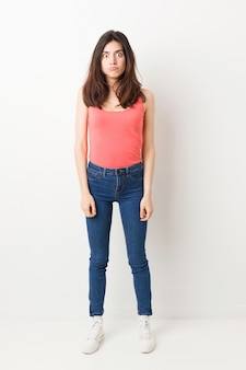 Full body young woman on white background shrugs shoulders and open eyes confused.