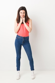 Full body young woman on white doubting between two options.
