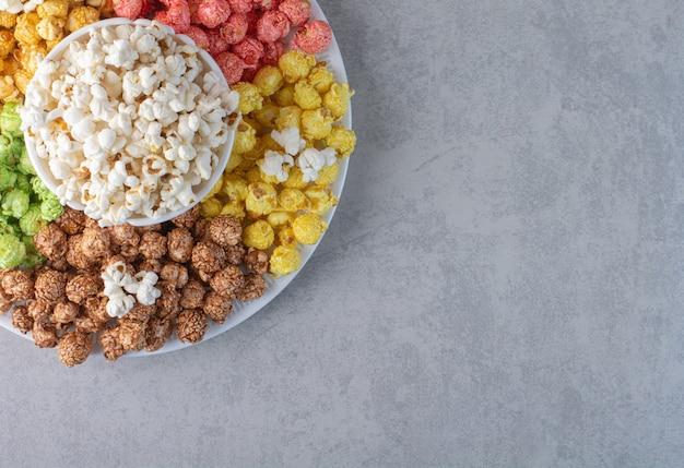 Полная миска попкорна с рассыпанной стопкой на куске ткани на мраморе.
