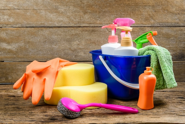 Full box of cleaning supplies and gloves on wooden background