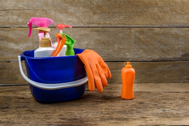 Full box of cleaning supplies and gloves on wooden table background