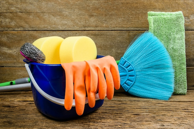 Full box of cleaning supplies, mop, broom and gloves on wooden floor background