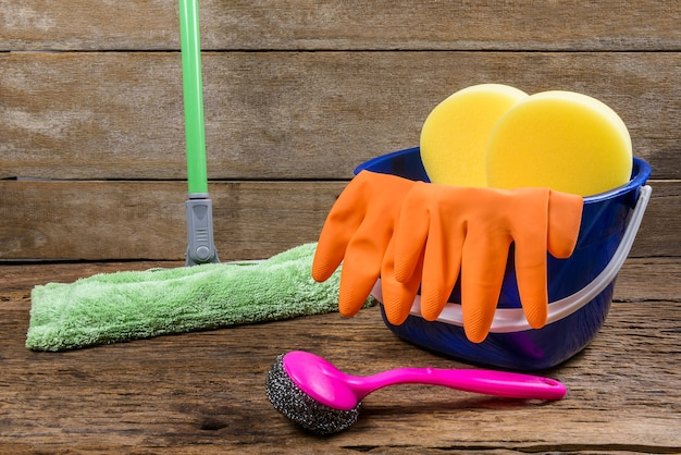 Full box of cleaning supplies, mop and gloves on wooden background