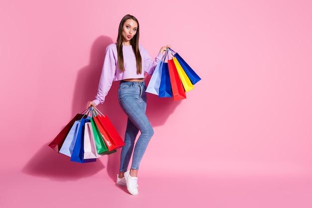 夢のような軽薄な女の子の完全な男の子の写真は、多くのバッグを持って買い物を楽しんでいますパステルカラーの背景の上に分離されたエアキスウェアライラックスタイルのスタイリッシュなトレンディなジャンパーデニムジーンズを送信します