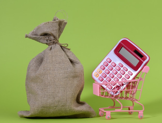 Full canvas bag, pink plastic calculator in a miniature metal shopping cart against a green surface. the concept of wealth, savings on purchases, cashback from purchases