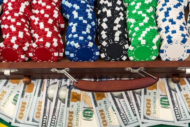 Полный ящик покерных фишек с долларами на игровом столе. покер.