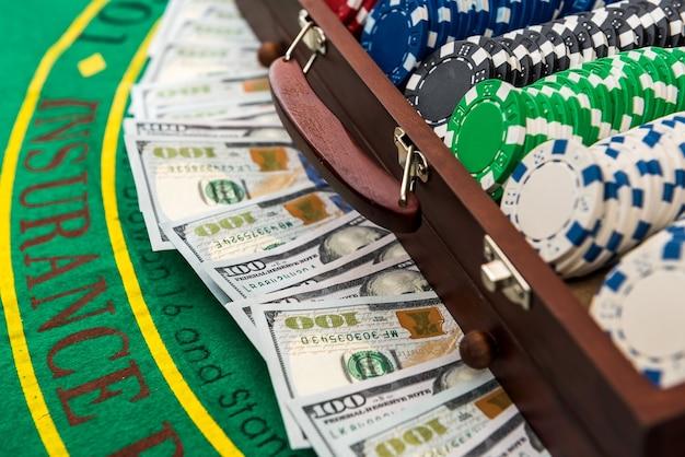 게임 테이블에 달러가있는 포커 칩의 전체 케이스