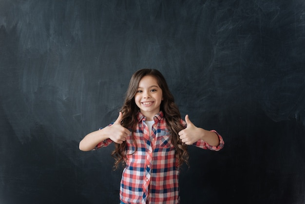 Full of cheerful emotions. positive upbeat little kid standing in blackboard and enjoying imaginary drawing while holdig thumbs up