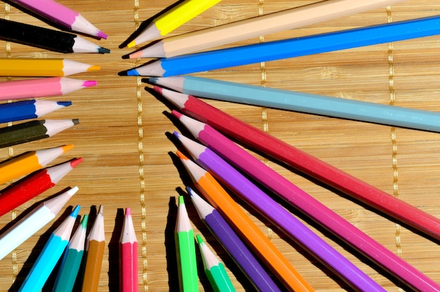 Full color pencils laid out in the shape of an ellipse on a wooden table.