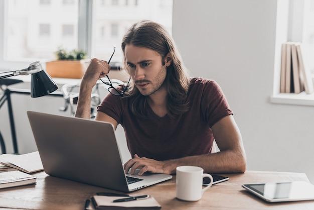 仕事で完全に集中。彼の眼鏡を運び、オフィスの彼の職場に座っている間ラップトップを見ている長い髪の自信を持って若い男
