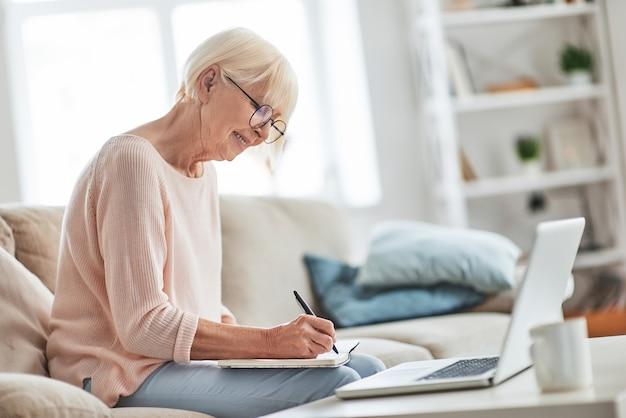 Полная концентрация. красивая старшая женщина что-то записывает