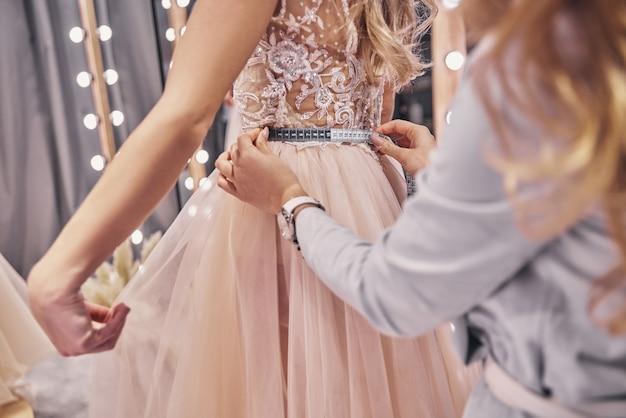 완전 집중. 피팅 룸에 서 있는 동안 그녀의 여자 친구의 허리를 측정 하는 젊은 여자의 클로즈업