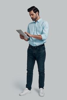 完全な集中。灰色の背景に立っている間デジタルタブレットを使用して作業している若い男の全長